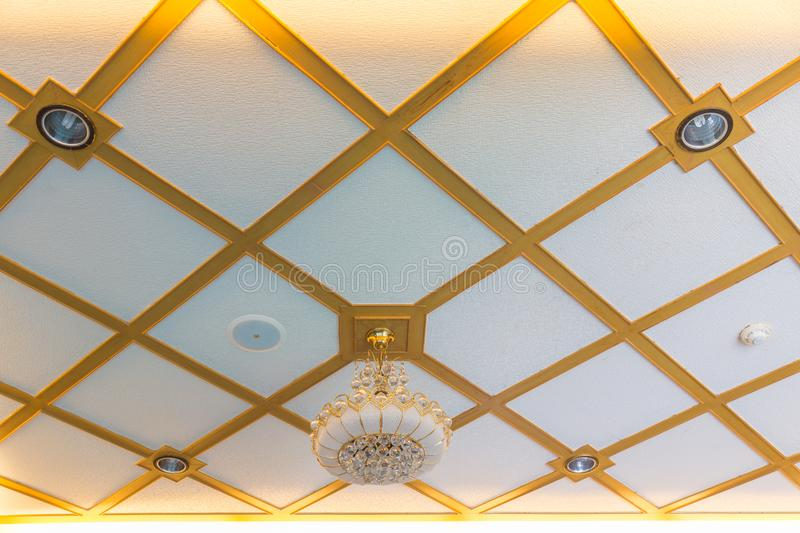 A Luxury glass Hanging lamp golden border on White and gold ceiling royalty free stock photography