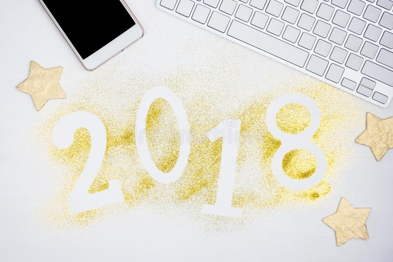 Luxury glowing numbers 2018 made from gold shiny glitter on white table with keyboard and and cell phone. New year concept. Text space royalty free stock photo