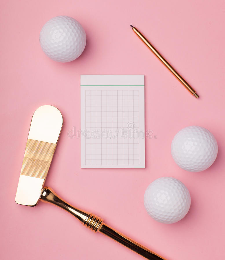 Luxury gold golf club and balls. Blank notepad surrounded luxury golden golf club with golf balls isolated on pink background stock image