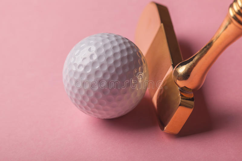 Luxury gold golf club and balls. Head of luxury golden golf club near golf ball on pink background royalty free stock images