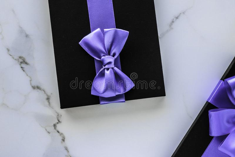 Luxury holiday gifts with lavender silk ribbon and bow on marble background stock image