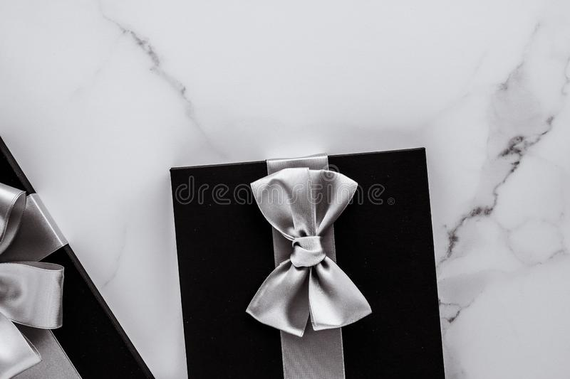 Luxury holiday gifts with silver silk ribbon and bow on marble background royalty free stock photo