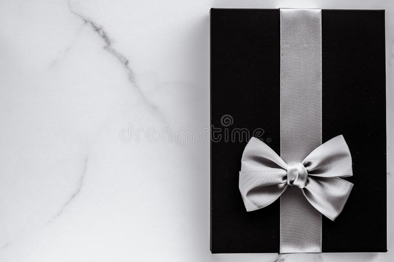 Luxury holiday gifts with silver silk ribbon and bow on marble background stock image