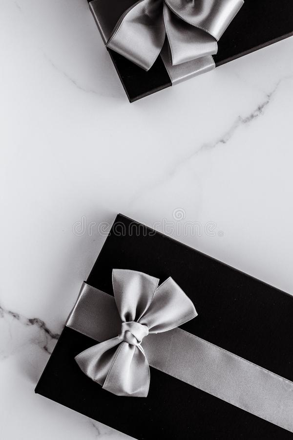 Luxury holiday gifts with silver silk ribbon and bow on marble background stock images