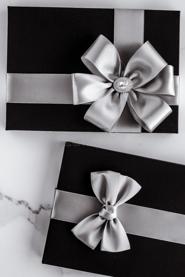 Luxury holiday gifts with silver silk ribbon and bow on marble background royalty free stock photos