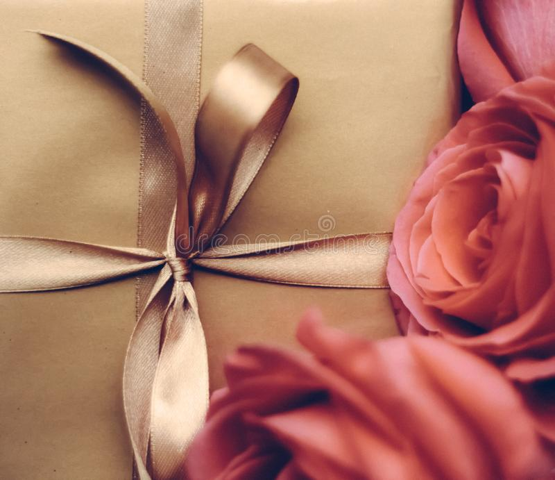 Luxury holiday golden gift box and bouquet of roses as Christmas, Valentines Day or birthday present. Vintage design, shop sale promotion and happy surprise stock photography