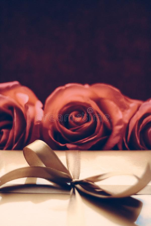 Luxury holiday golden gift box and bouquet of roses as Christmas, Valentines Day or birthday present. Vintage design, shop sale promotion and happy surprise stock photo