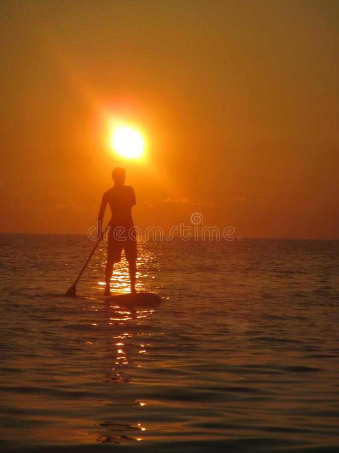 SUP - Stand Up Paddling in the sunset - Maldives royalty free stock images