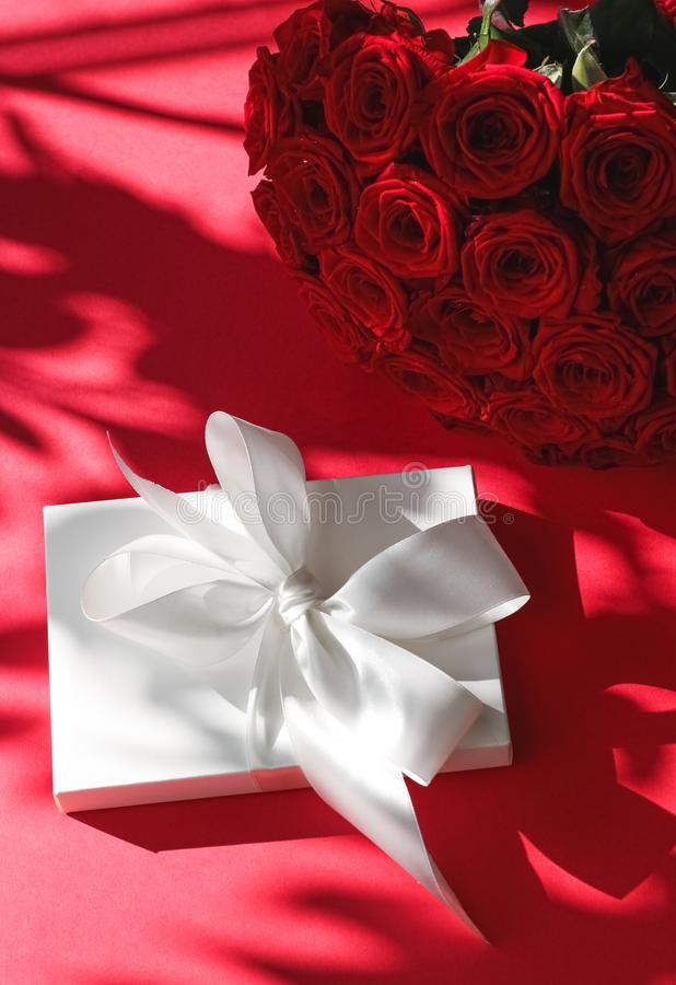 Luxury holiday silk gift box and bouquet of roses on red background, romantic surprise and flowers as birthday or Valentines Day royalty free stock image