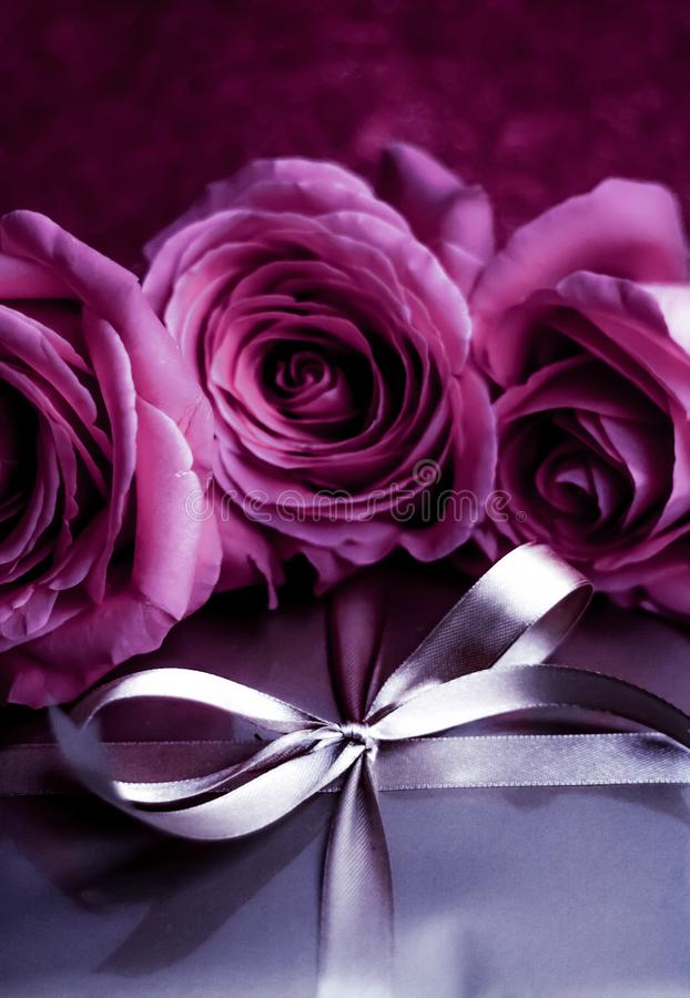 Luxury holiday silver gift box and pink roses as Christmas, Valentines Day or birthday present. Luxurious design, shop sale promotion and happy surprise concept royalty free stock photography