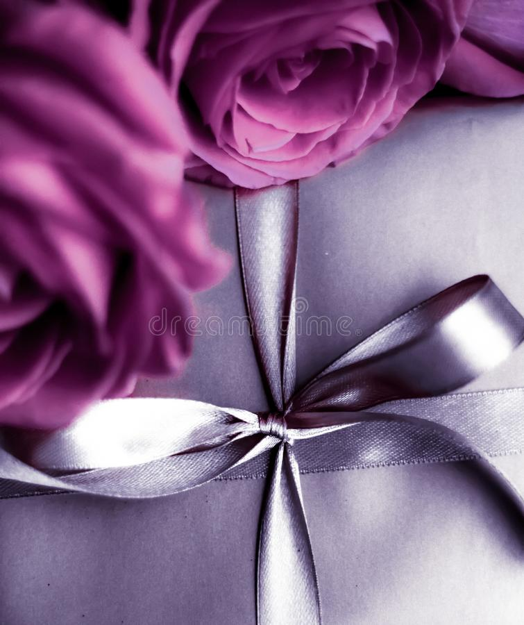 Luxury holiday silver gift box and pink roses as Christmas, Valentines Day or birthday present. Luxurious design, shop sale promotion and happy surprise concept stock image