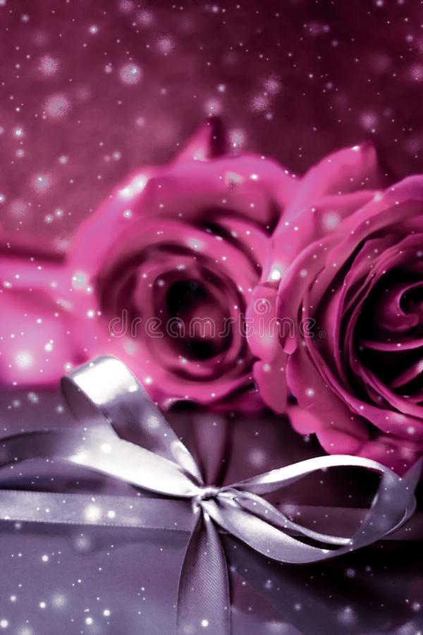 Luxury holiday silver gift box and pink roses as Christmas, Valentines Day or birthday present. Luxurious design, shop sale promotion and happy surprise concept stock images
