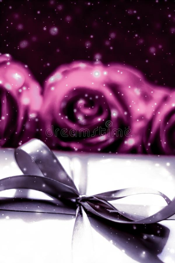Luxury holiday silver gift box and pink roses as Christmas, Valentines Day or birthday present. Luxurious design, shop sale promotion and happy surprise concept stock photography