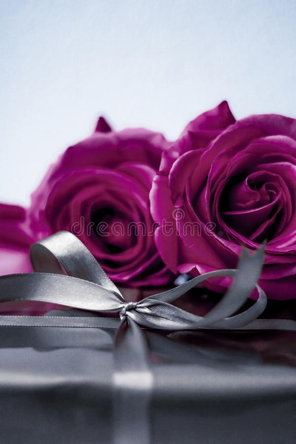 Luxury holiday silver gift box and purple roses as Christmas, Valentines Day or birthday present. Luxurious design, shop sale promotion and happy surprise royalty free stock photo