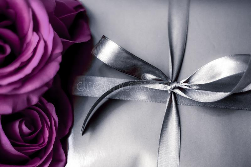 Luxury holiday silver gift box and purple roses as Christmas, Valentines Day or birthday present. Luxurious design, shop sale promotion and happy surprise stock photo