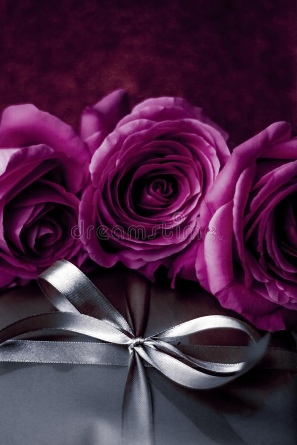 Luxury holiday silver gift box and purple roses as Christmas, Valentines Day or birthday present. Luxurious design, shop sale promotion and happy surprise royalty free stock photography