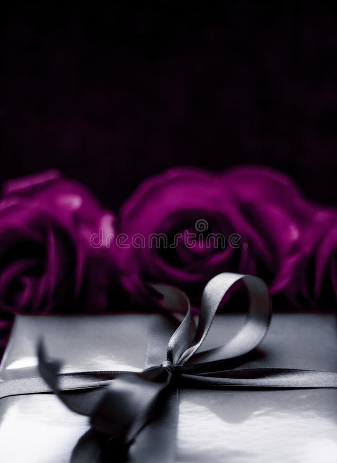 Luxury holiday silver gift box and purple roses as Christmas, Valentines Day or birthday present. Luxurious design, shop sale promotion and happy surprise stock image