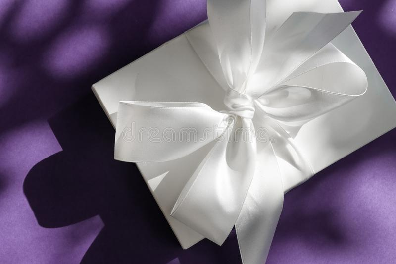 Luxury holiday white gift box with silk ribbon and bow on violet background, luxe wedding or birthday present stock photos