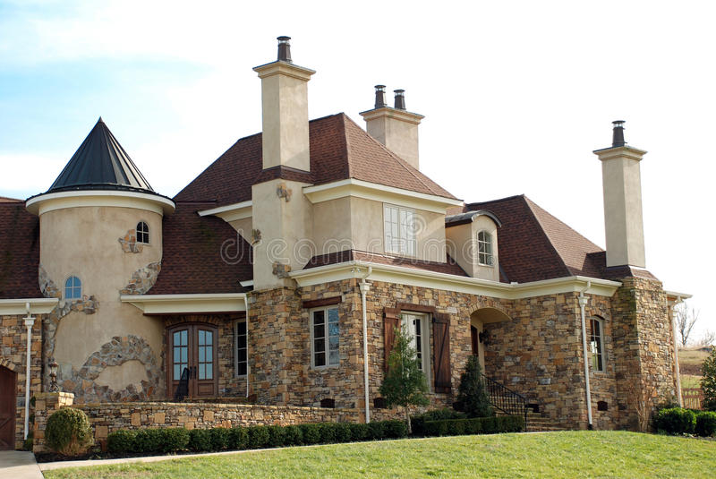 Luxury Home 67. A two-story home turrets, unique stone facade and numerous chimneys stock images