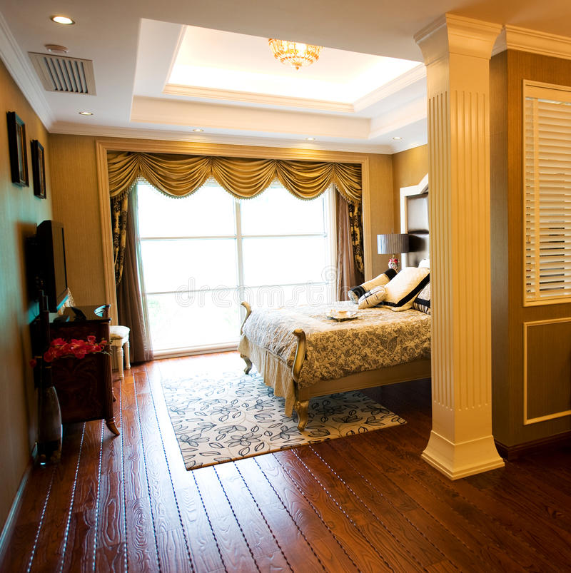 Luxury home bedroom. Comfortable bedroom in a luxury home with stylish decor royalty free stock image