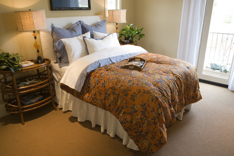 Luxury home bedroom. Comfortable bedroom in a luxury home with stylish decor stock images