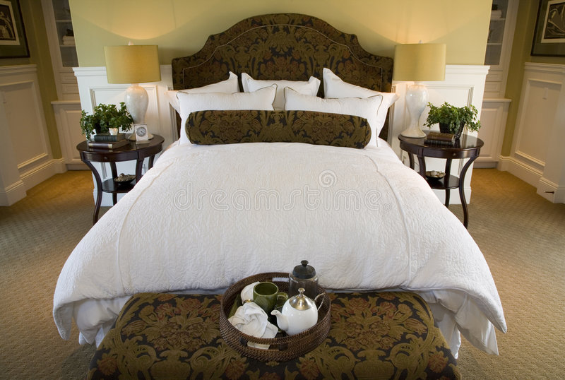 Luxury home bedroom. Luxury home bedroom with stylish furniture and decor royalty free stock images