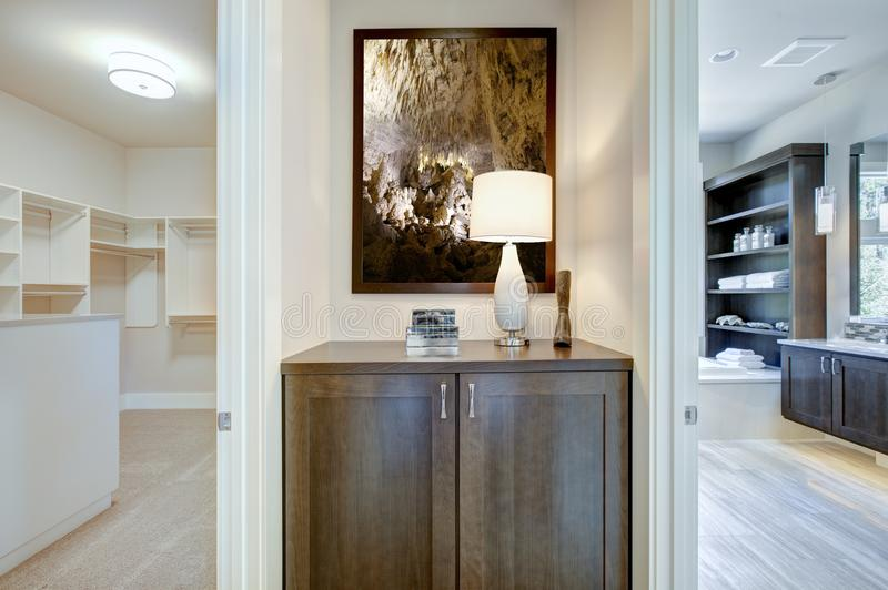 Luxury home interior, view of bathroom and a walk-in closet. Chic home interior features a taupe wood cabinet lined with a white table lamp placed under a royalty free stock photos