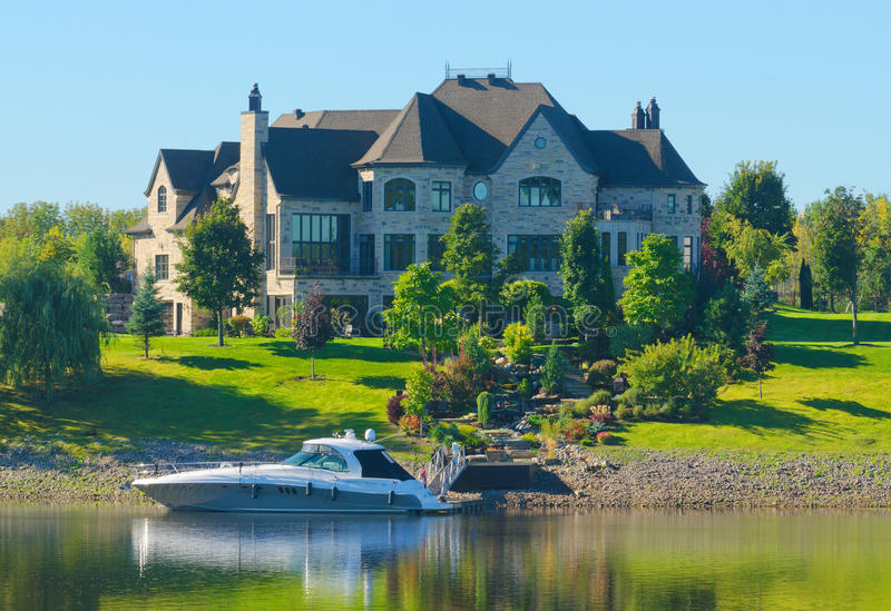 Luxury Home by the Lake. Luxury home with beautiful landscape by the lake with boat stock photography