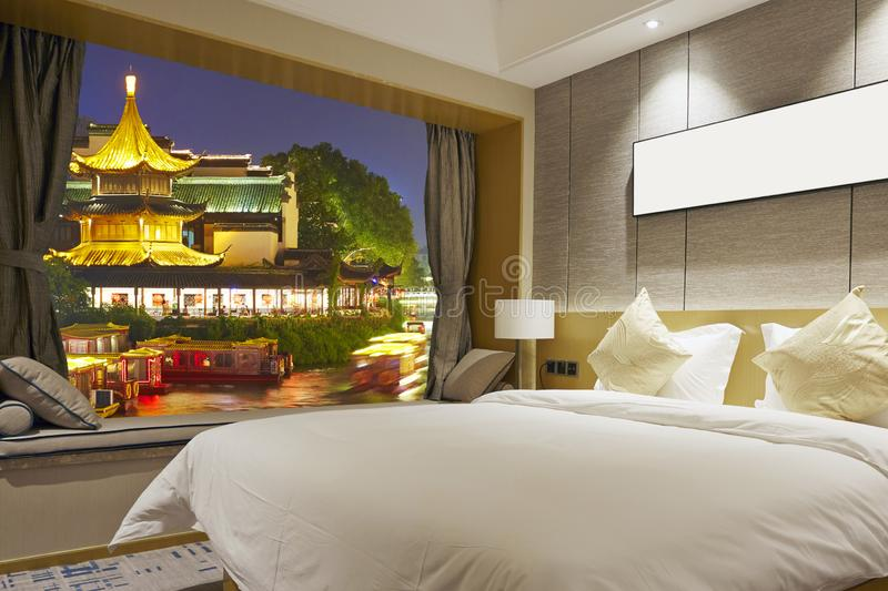 Luxury room and Nanjing ancient buildings through window. Luxury hotel room with big window, kingbed and