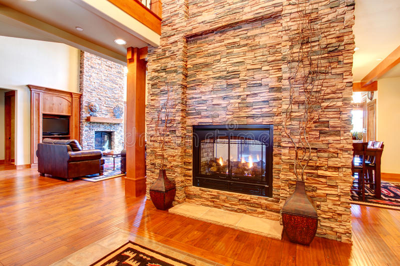 Luxury house interior. Stone wall with fireplace. Beautiful stone wall with built-in fake fireplace. Two vases with dry branches complete the wall look royalty free stock images
