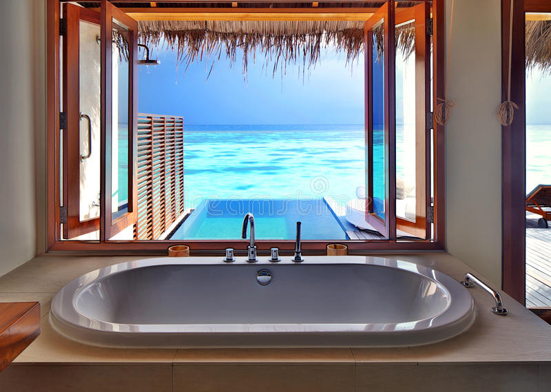 Luxury interior on beach resort. Luxury beautiful interior design on beach resort, window view from bathroom on clear blue sea, summer vacation on Maldives stock photo
