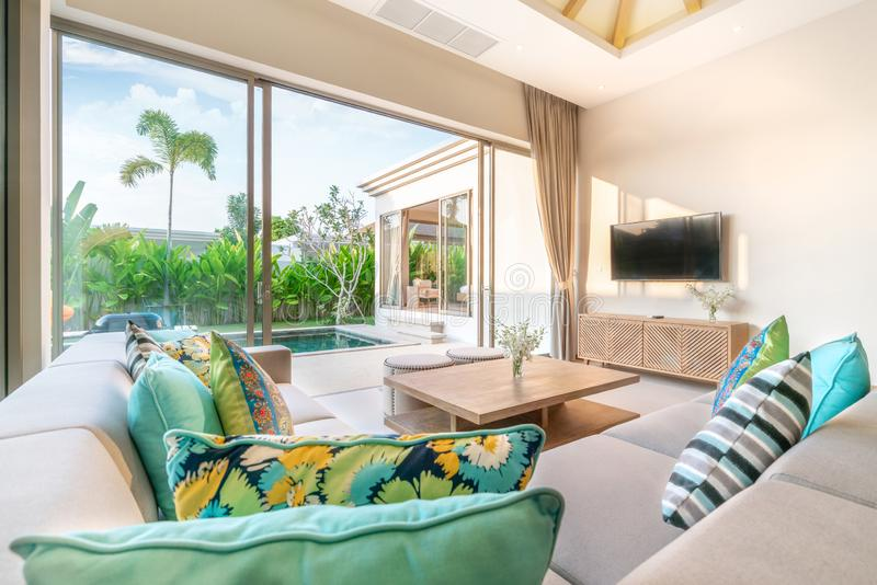 Luxury interior design in living room of pool villas. Airy and bright space with high raised ceiling, sofa, middle table, dining. Luxury interior design in stock photography