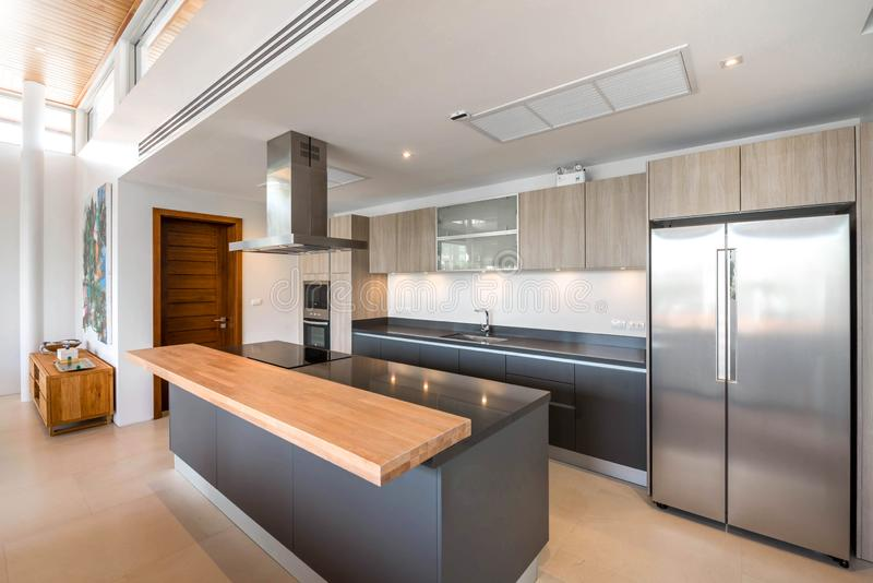 Luxury interior design pool villa in kitchen area which feature island counter and built in furniture in the house or home. Luxury interior design pool villa in royalty free stock images