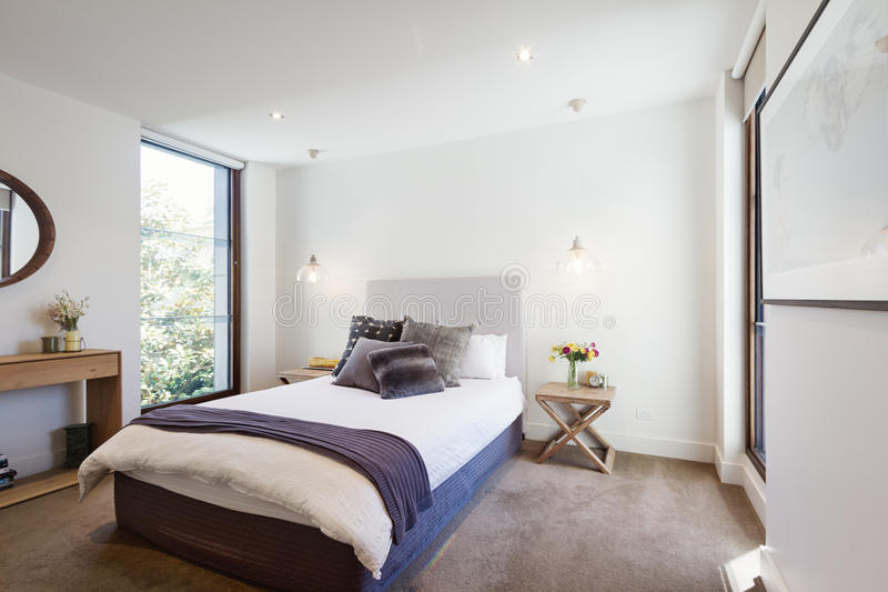 Luxury interior designed bedroom with comfy pillows and throw ru stock photography