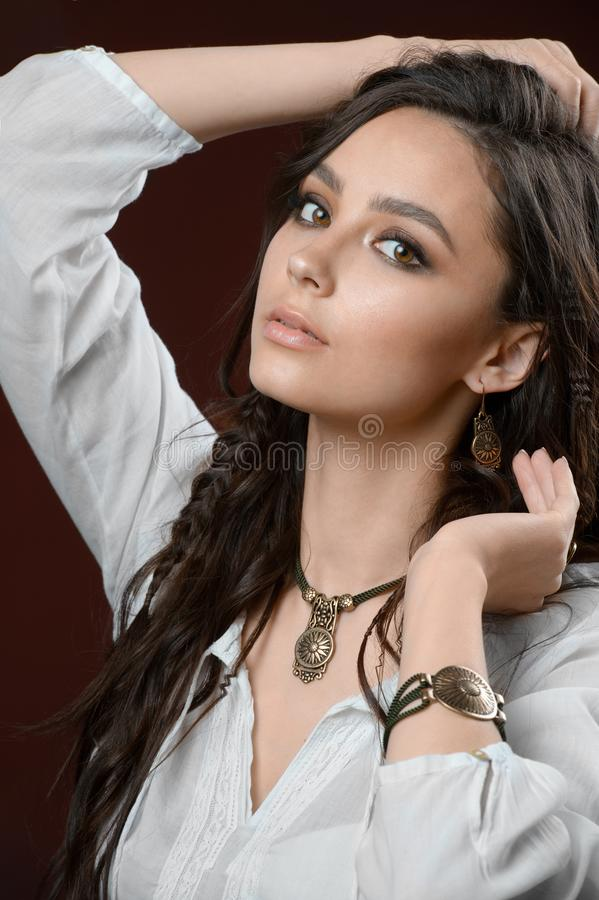 Luxury jewelry and fashion concept. A model with stylish collection - bracelet earrings necklace on brown background. The luxury jewelry and fashion concept. A royalty free stock image
