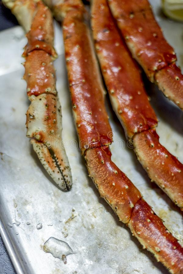 King snow crab`s claw with lemon at metal tray on black background royalty free stock photography