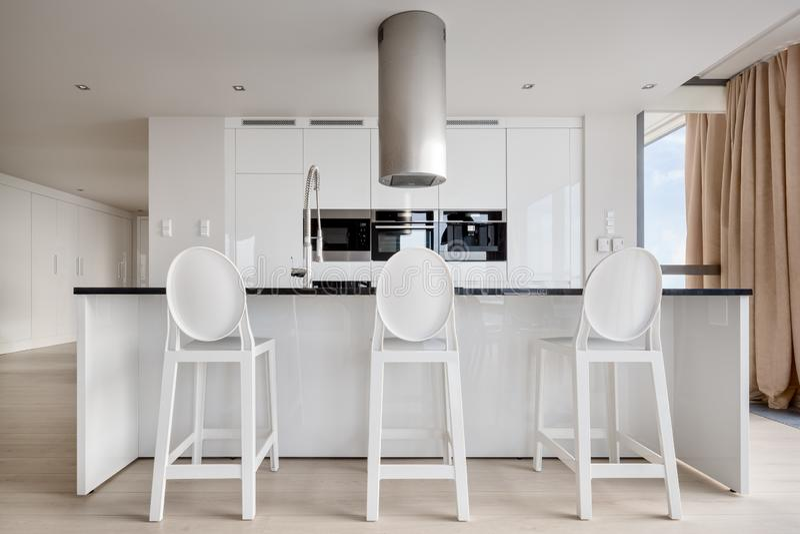 Luxury kitchen area in white. Luxury and shiny kitchen area in black and white with elegant chairs royalty free stock photos