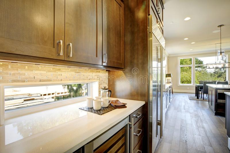 Luxury kitchen with a glass door wine cooler. Luxury kitchen features brown wood front upper cabinets and shaker lower cabinets fitted with a glass door wine royalty free stock photography
