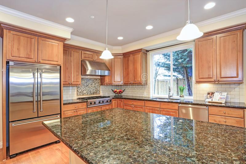 Luxury kitchen fitted with Viking appliances. Luxury kitchen with an island, light wood cabinets and Viking appliances royalty free stock images