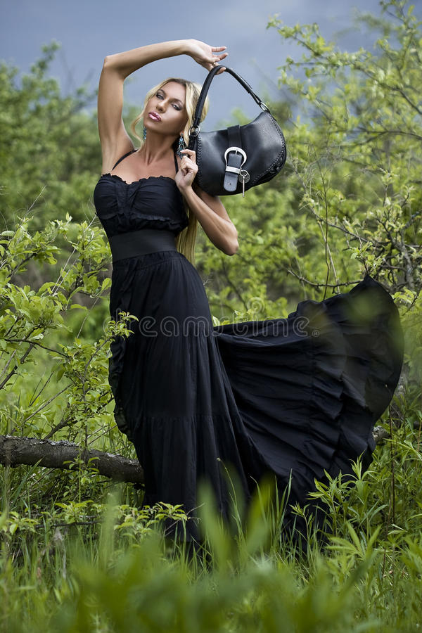 The luxury lady in a black dress. In green park royalty free stock images