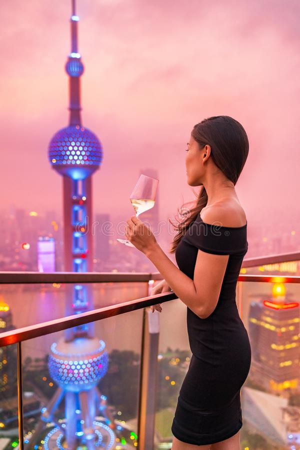 Luxury lifestyle Shanghai city Asian woman drinking white wine glass at rooftop bar party night rich club vip nightclub. Elegant stock image