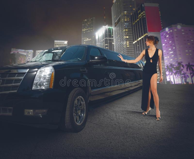 Luxury limousine. Rich woman touches and admires her limousine royalty free stock image