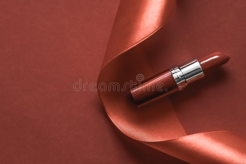 Luxury lipstick and silk ribbon on bronze holiday background, make-up and cosmetics flatlay for beauty brand product design. Cosmetic branding, glamour lip gloss stock photo