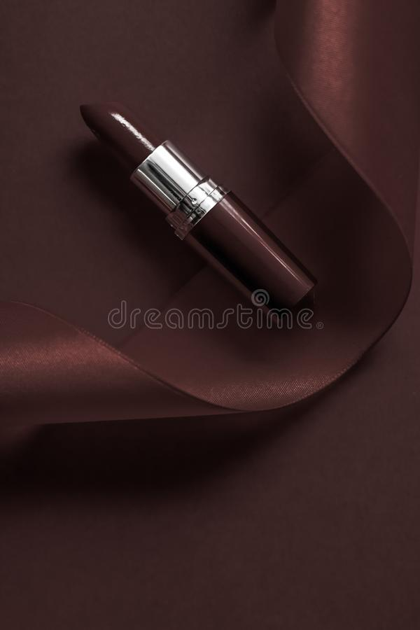 Luxury lipstick and silk ribbon on chocolate holiday background, make-up and cosmetics flatlay for beauty brand product design. Cosmetic branding, glamour lip stock photography
