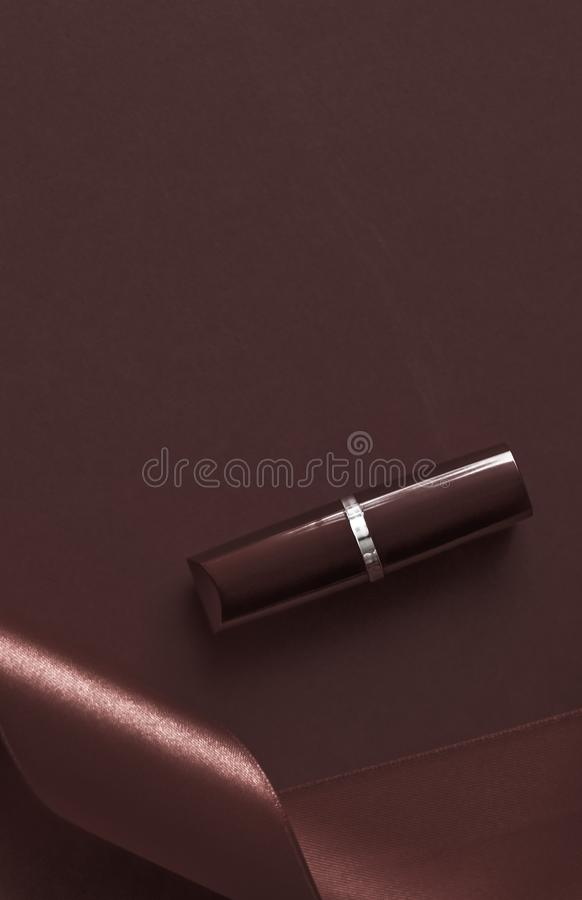 Luxury lipstick and silk ribbon on chocolate holiday background, make-up and cosmetics flatlay for beauty brand product design. Cosmetic branding, glamour lip royalty free stock photo