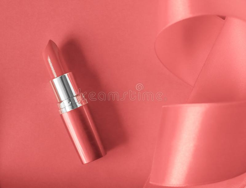 Luxury lipstick and silk ribbon on coral holiday background, make-up and cosmetics flatlay for beauty brand product design. Cosmetic branding, glamour lip gloss stock photography