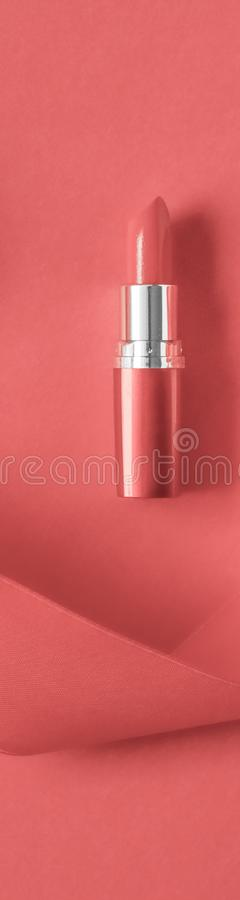 Luxury lipstick and silk ribbon on coral holiday background, make-up and cosmetics flatlay for beauty brand product design. Cosmetic branding, glamour lip gloss stock image