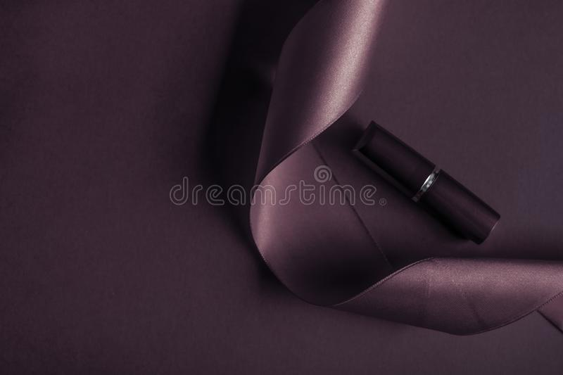 Luxury lipstick and silk ribbon on dark purple holiday background, make-up and cosmetics flatlay for beauty brand product design. Cosmetic branding, glamour lip royalty free stock photo
