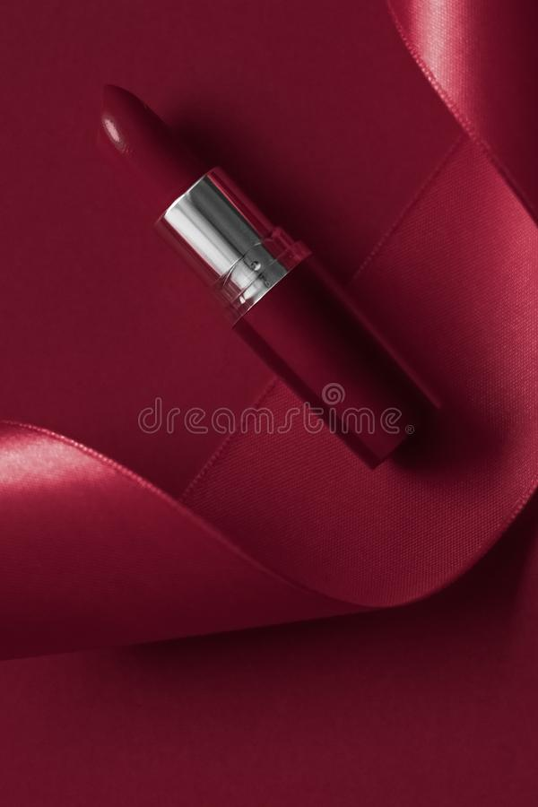 Luxury lipstick and silk ribbon on maroon holiday background, make-up and cosmetics flatlay for beauty brand product design. Cosmetic branding, glamour lip gloss royalty free stock photo