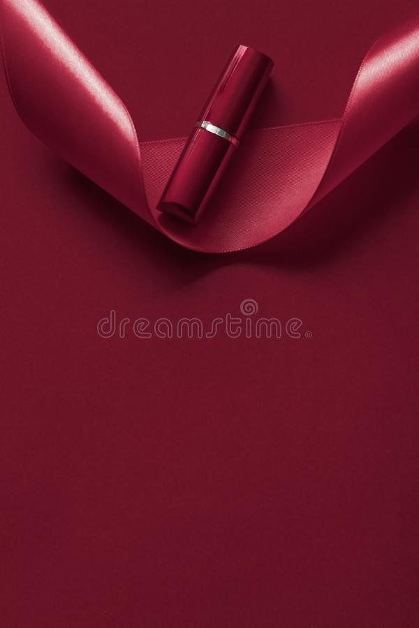 Luxury lipstick and silk ribbon on maroon holiday background, make-up and cosmetics flatlay for beauty brand product design. Cosmetic branding, glamour lip gloss royalty free stock photography
